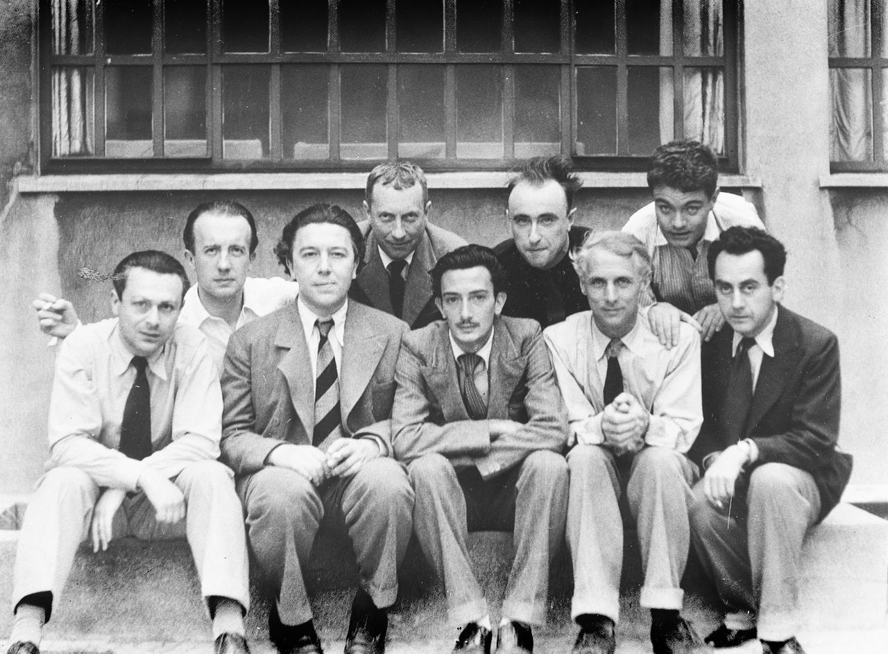 De izquierda a derecha: Tristan Tzara, Paul Eluard, André Breton, Hans Arp, Salvador Dalí, Yves Tanguy, Max Ernst, René Crevel, Man Ray.