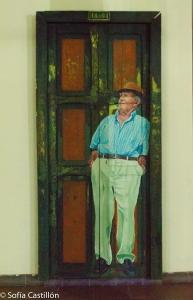 En una puerta de la Casa de la Cultura de El Santuario, un hombre pintado con detalle. Se encuentra de pie y usa sombrero.
